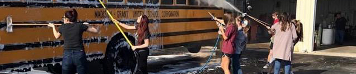 students washing a bus