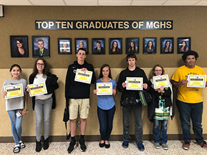 7 students of the week in front of Top Ten Graduates of MGHS sign