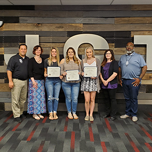 Graduates of the adult cosmetology program pose together with their certificates
