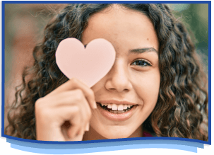 smiling girl holding a paper heart