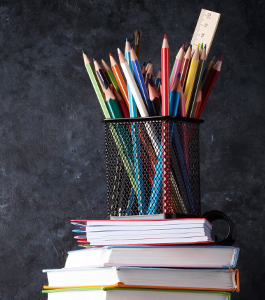 Colored pencils and a ruler in a container on top of stacked books