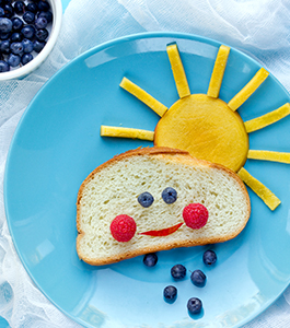 Fruit in the shape of a sun and bread in the shape of a cloud with a smiley face formed by fruit