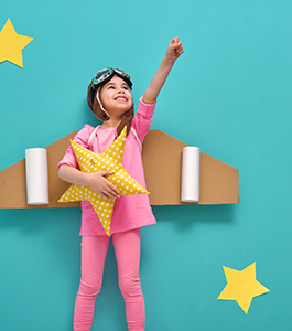 Girl dressed in an airplane and pilot costume holds up her fist as her other hand holds a star pillow