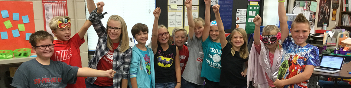 Students and teacher make a superhero pose