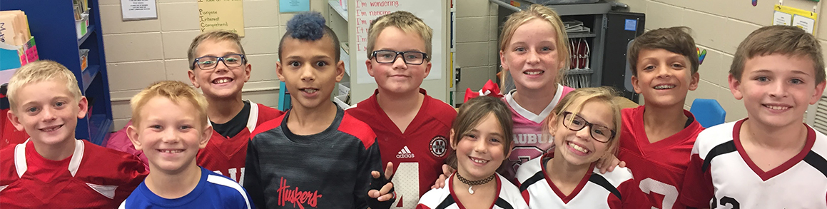 Students in sports jerseys stand smiling together