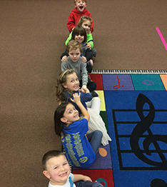 Kids sit forming a line on a carpet with decorative musical notes
