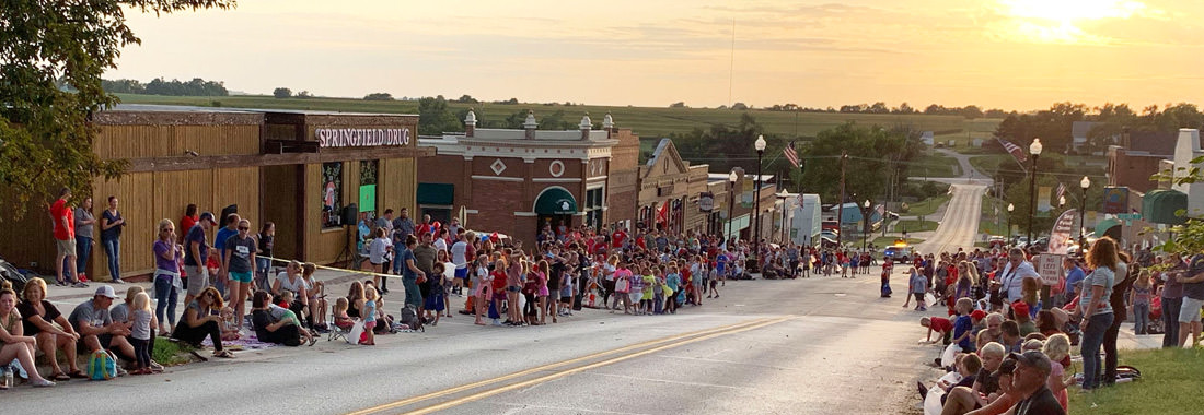 Adults and children lined up along the street curb for an event