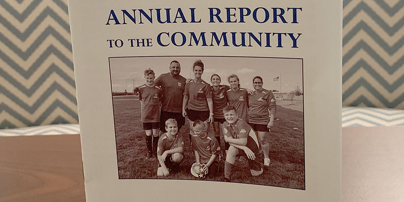 Annaul Report to the Community flyer with a group of soccer players on the front