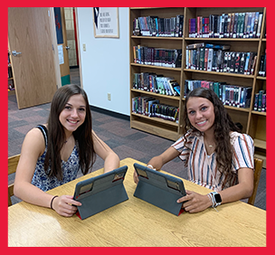 Two girls use tablets in a library
