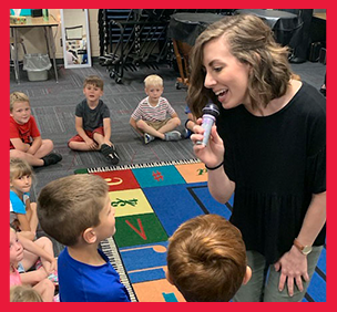 Staff member sings to students using a small microphone in a classroom