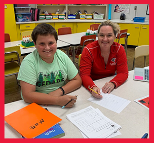 Staff member helps student completing classwork