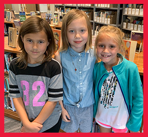 Three female students pose together in a library