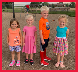 Four students pose together on a playground