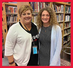 Two staff members pose together in a library