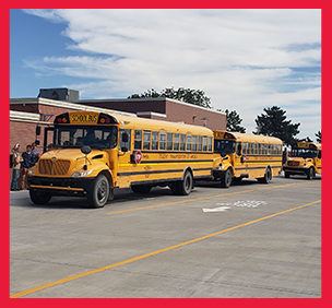 Row of school buses in front of a school