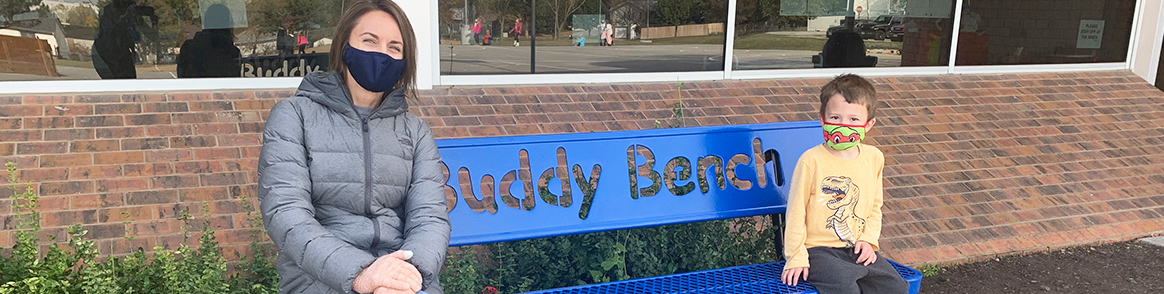 Teacher sitting with student on the blue bench with words Buddy Bench