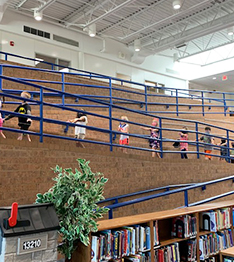 elementary students having fun walking up the ramp from the school library