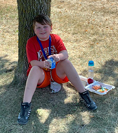 young student in red under a tree with his lunch