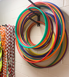 Jumping ropes and hula hoops hanging on gym wall ready for students