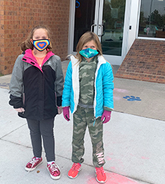 Two happy students in winter gear and face masks outside school building