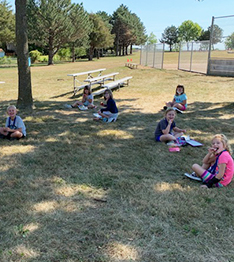 Young students enjoying their lunch outside while practicing safe social distancing