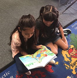 Two female students sitting on classroom rug reading a book