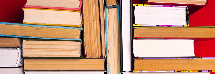 Hardcover books stacked on top of each other behind a bright red background