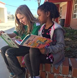 Two students reading books outside