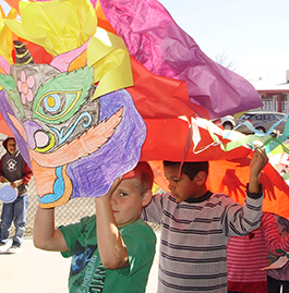 Student holding paper dragon above his head with students behind him