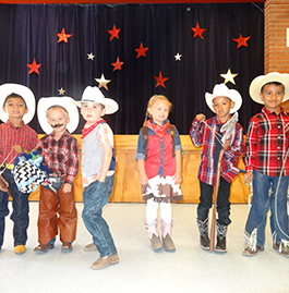 Students in cowboy attire stand in front of a stage