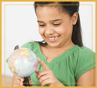 Smiling student touching a globe