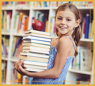 Smiling female student holds a stack of books with an apple on top