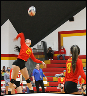 Volleyball player throws a volleyball over a net