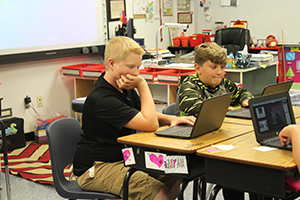 Two elementary school boys sitting at their desk and concentrating on their assignments