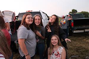 Group of happy students enjoying back-to-school bonfire
