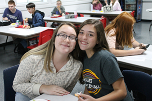Two girl students smiling in class together