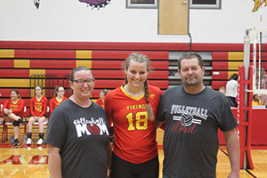Senior volleyball athlete posing for a picture with her parents