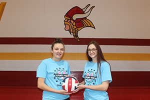 Two female volleyball players holding a ball
