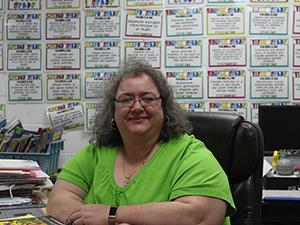 Ms. Grajek poses at her desk