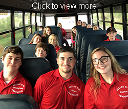 Smiling students sit on a bus