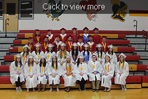 Click to view more. Graduates pose together on gym bleachers.
