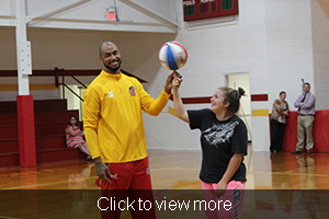 Tomahawk helps a female student hold a basketball on her finger