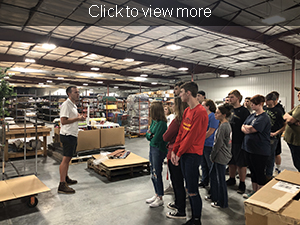 Students listen to guide as he speaks in the warehouse