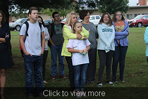 Woman wraps her arms around a young girl in an embrace as they stand on the grass with other people