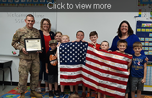 Click to view more. SSG Robert Gardner poses with students and staff as they hold a large American flag.