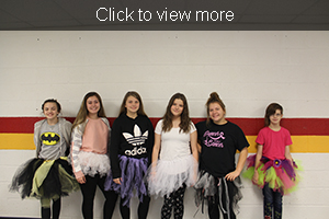 Six students wearing tutus pose together