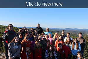 Students and teachers pose together on the mountain