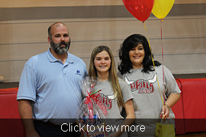 Volleyball player holds up a gift basket as she stands next to two adults, one holding balloons and a gift bag