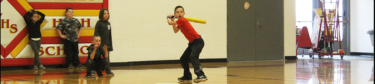 Students in gymnasium one student swings baseball bat