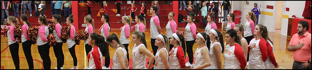 Athletic students during national anthem in gym